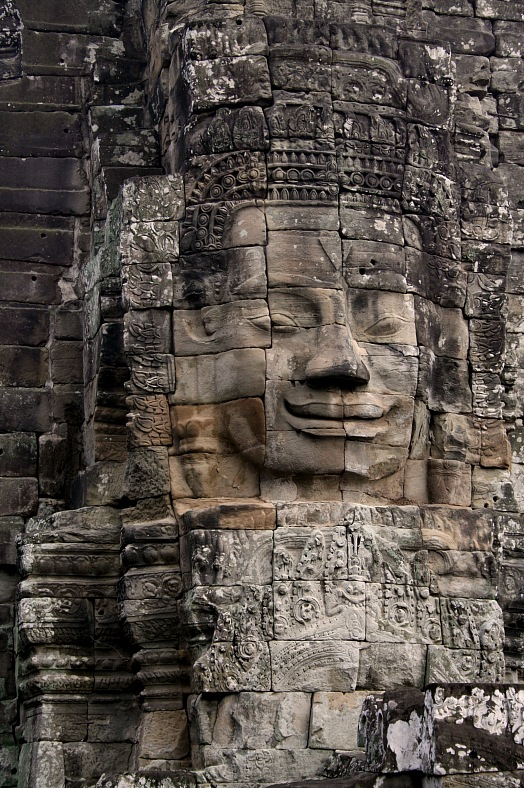 Cambodia tourism. Stone carved face on a wall in a temple in Angkor Wat. Cambodia vacations.