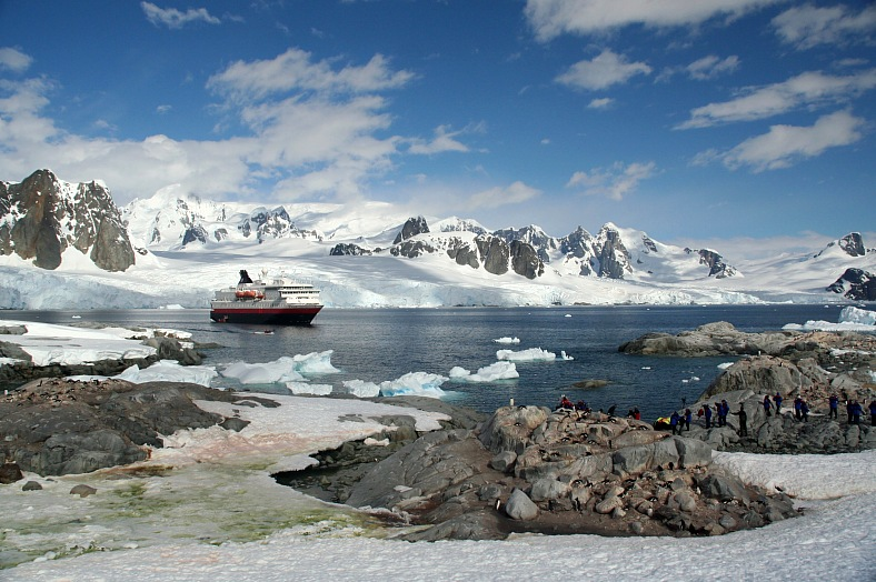 Antarctic tourism. Cruise ship & tourists amid icebergs and glaciers. Petermann Island. Antarctica cruise.