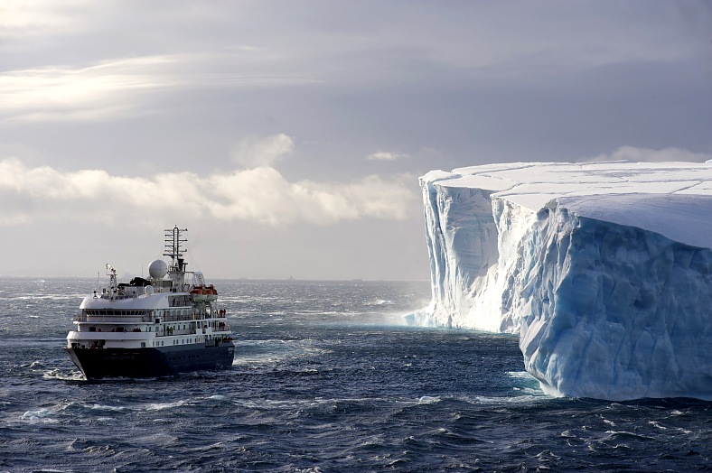 Antarctica cruise. The cruise ship Corinthian II in front of a huge Iceberg. Antarctica travel.