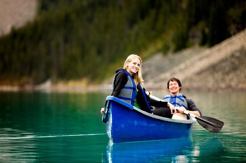 Banff national park travel Canada. Canoeing trip. Couple Canoeing and Relaxing. Banff Lake Louise tours Canada.