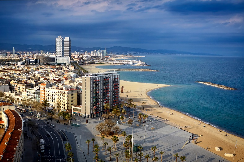 Spain travel. Aerial view over Barcelona coastline and beach. Shot from Montjuic cable car just before the rain