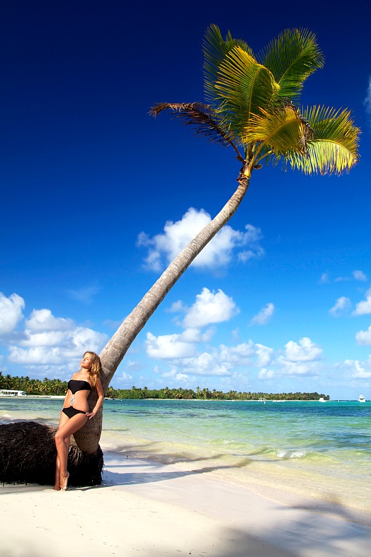 Caribbean vacations. Woman relaxing near palm tree on a Caribbean beach. Exotic vacations