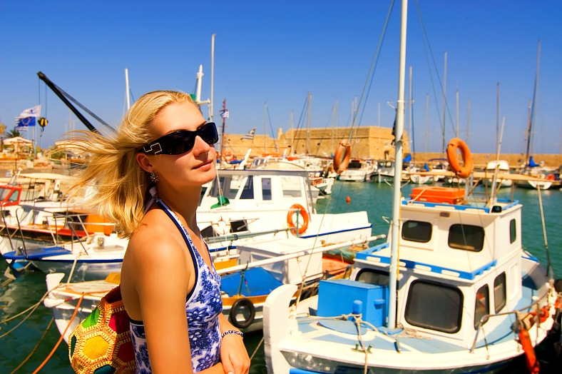 Crete vacations Greece. Beautiful blond girl in sunglasses near the yacht club. Greece islands, Crete.