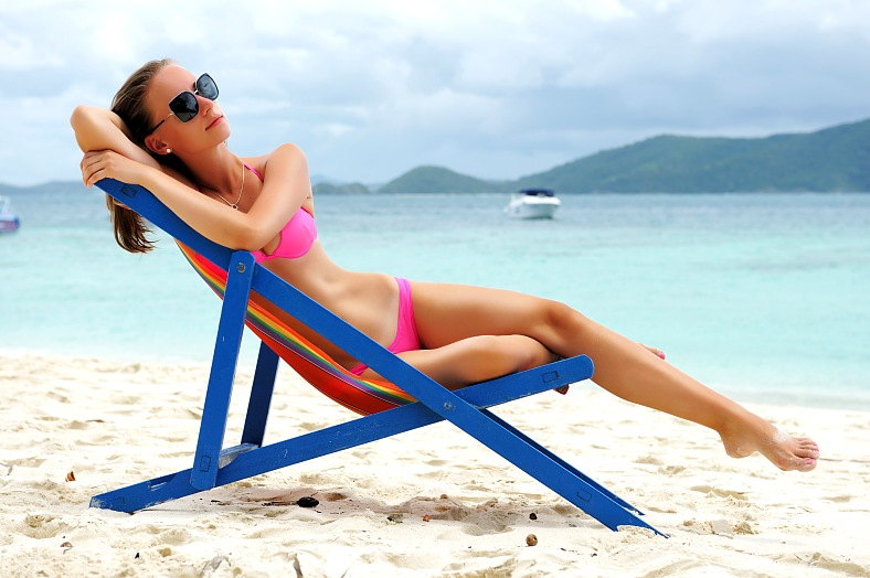 Girl on Thai beach. Tropical beach chaise lounge. Thailand island vacation - vacation travel photos