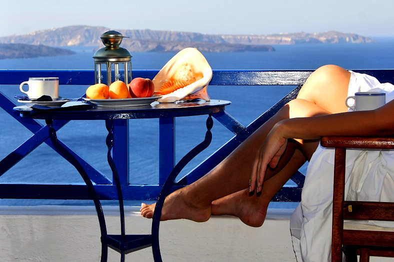 Greece travel. Relaxation with a seaview and fruit plate. Santorini island, Greece vacations.