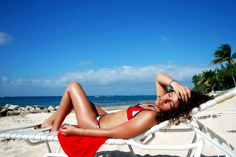 Grand Cayman vacation. The girl having sunbath on Seven Mile Beach. Grand Cayman resorts, Cayman Islands tours.
