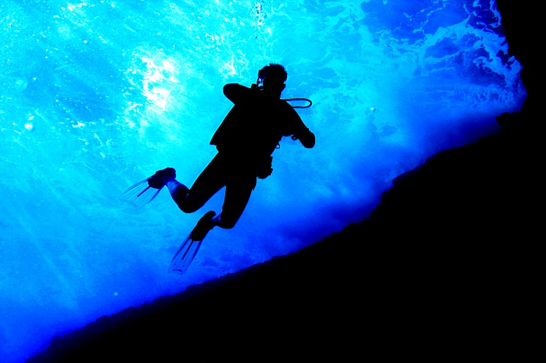 Hawaii diving tours. A scuba diver seen from below, silhouetted against sunlight and surface waves. Hawaii Scuba Diving.