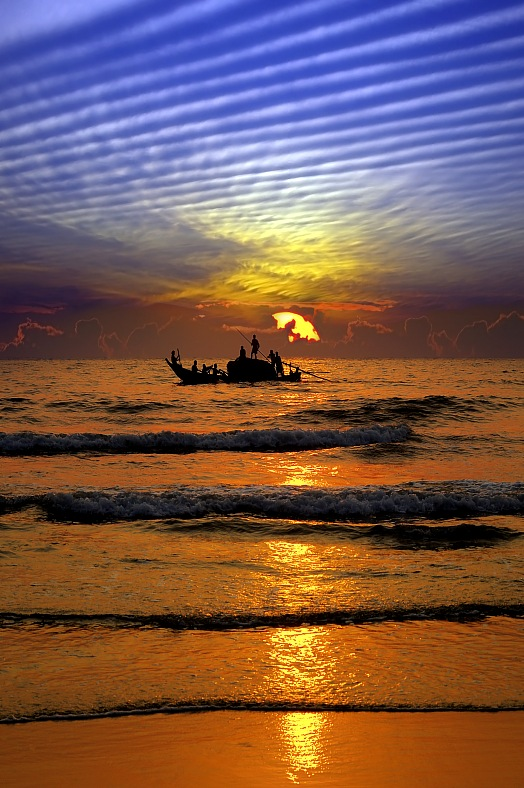 Fishing India vacations. Fishing boat at sunset on the background of the fantastic sky. India tours.