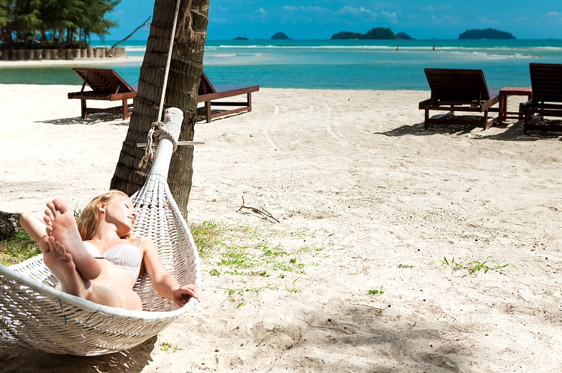 Thailand island vacation. Blonde woman asleep in a hammock. Ko Chang. Thai beach resorts