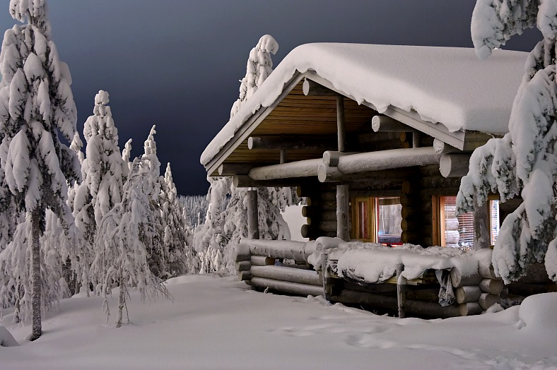 Lapland vacations Finland. Cozy cottage in winter forest. Laplandia tourism Finland.