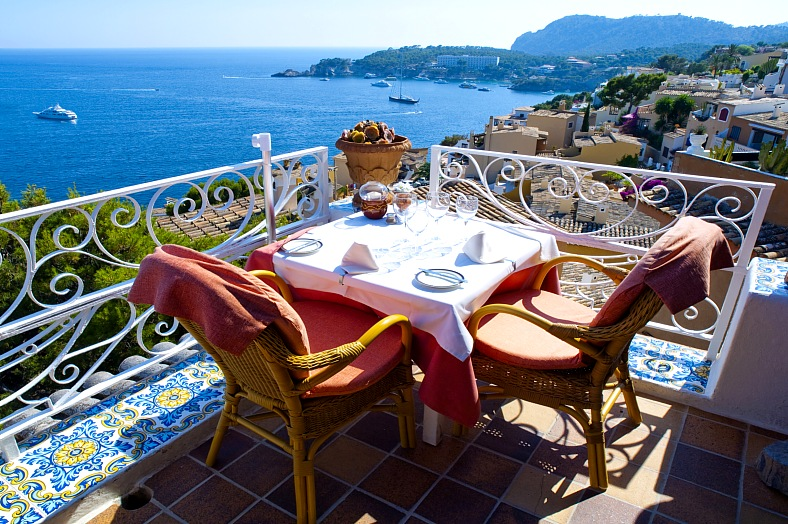 Mallorca vacations. Restaurant balcony in Mallorca with beautiful view to the Mediterranean Sea. Mallorca travel.
