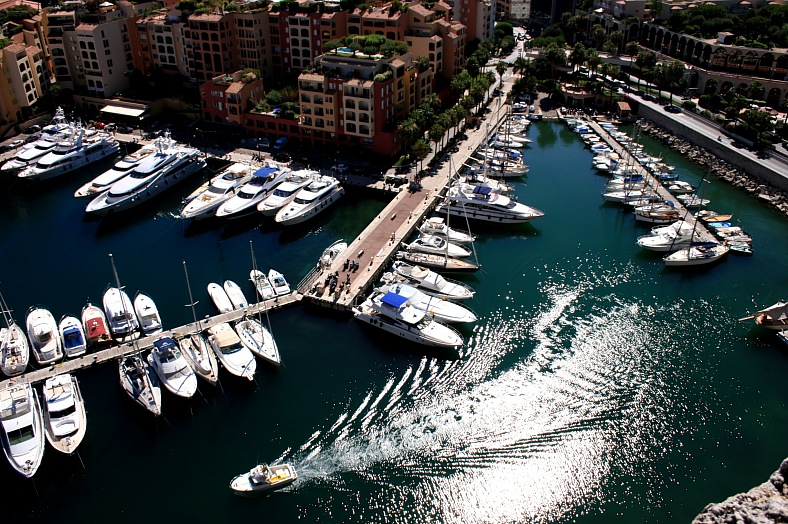 Monaco cruises. Waves reflecting sun astern of a speed-boat sailing near a pier in a Monaco port, view from above. Monaco tours.