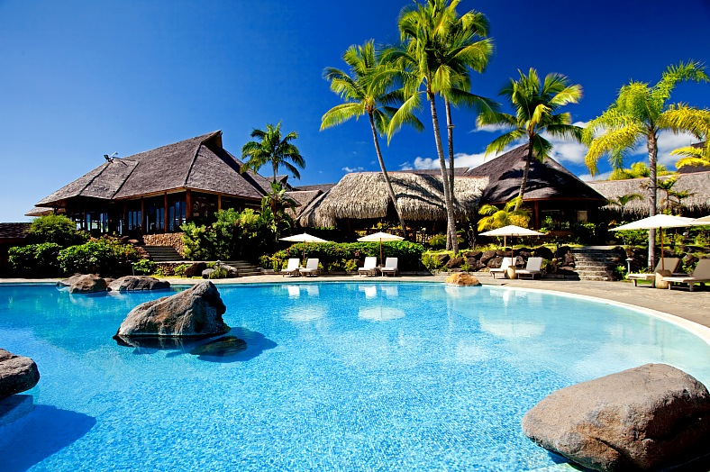 Moorea hotels, Tahiti. Palm trees hanging over stunning hotel pool with rocks. Moorea island, French Polynesia resort - vacation travel photos