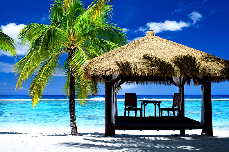 Cook Islands vacations Rarotonga. Tropical gazebo with chairs on amazing white sand beach. Rarotonga travel.