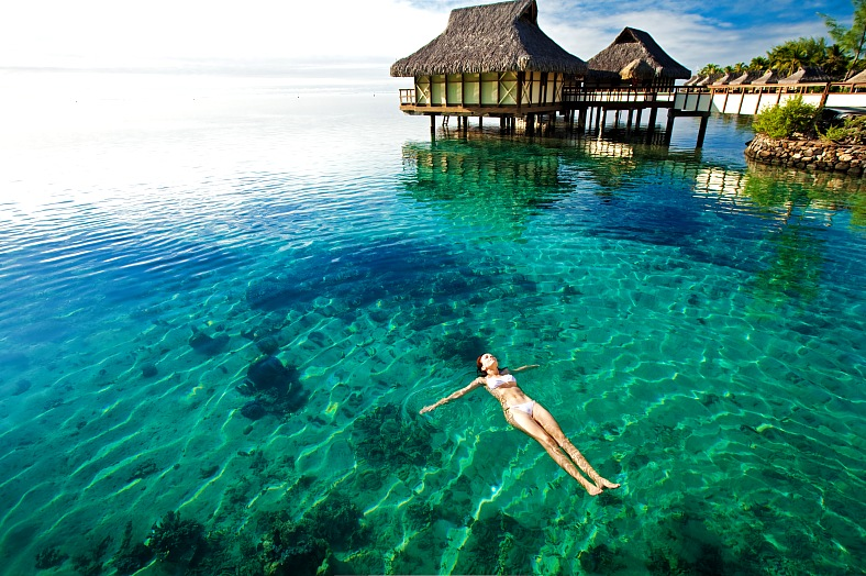 Moorea, Tahiti coral lagoon. Young woman in white bikini swimming in a coral lagoon. Moorea island travel - vacation travel photos