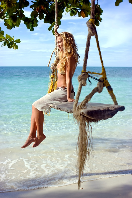 Thai vacations - Ko Samui island. Girl sitting on rope swings on the sandy beach. Thailand island vacation