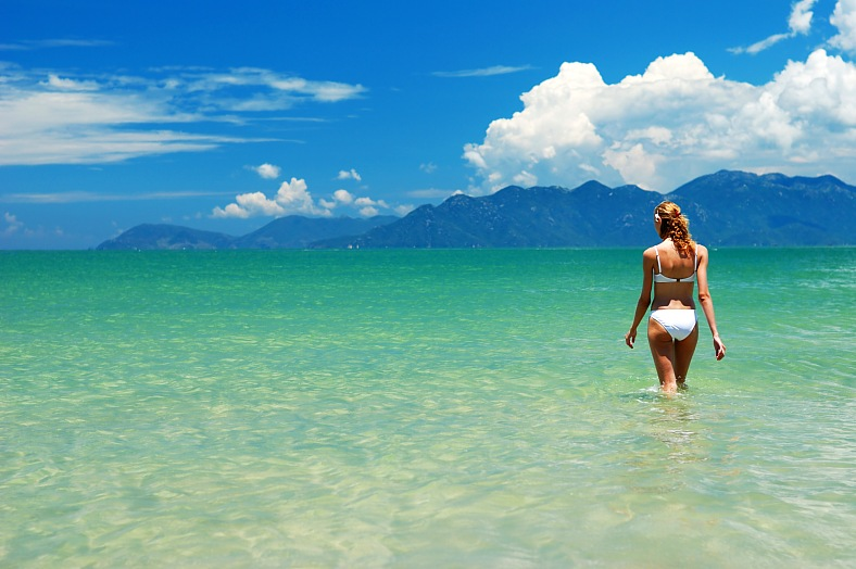 Vietnam beach vacations. Girl on a tropical beach in the sea. Vietnam tour packages.
