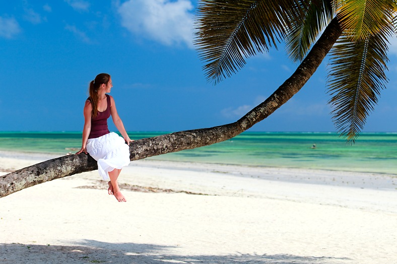 Tropical vacations - Zanzibar tours. Woman sitting on palm tree on exotic beach of Zanzibar island