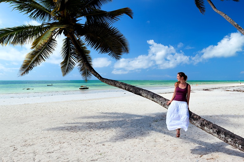 Zanzibar tropical tours. Woman on palm tree. Africa travel packages - exotic beach of Zanzibar island - vacation travel photos